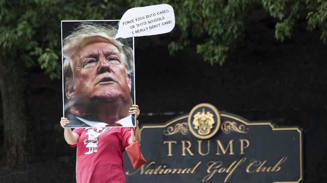 A protestor holds a sign as US President Donald Trump visits Trump National Golf Club in Sterling, Virginia, July 12, 2020. (Photo by SAUL LOEB / AFP)