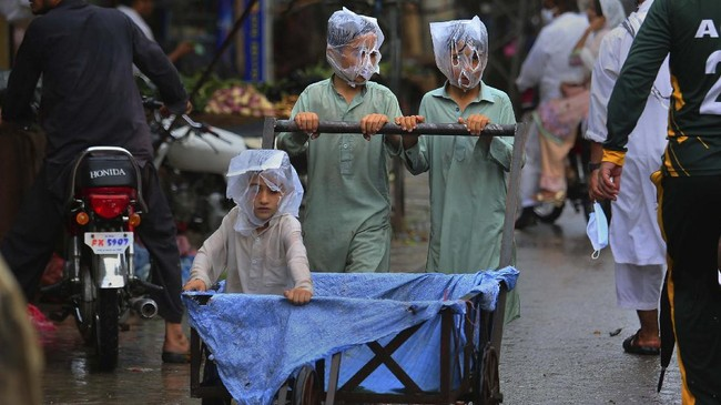 Youths cover their faces with plastic bags while pushing a handcart during rainfall in Peshawar, Pakistan, Sunday, July 12, 2020. (AP Photo/Muhammad Sajjad)
