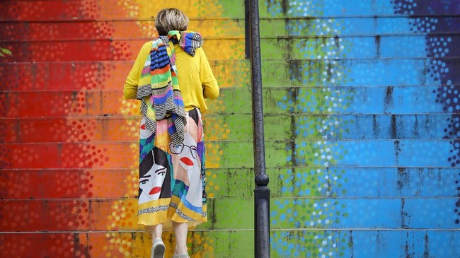 A woman walks up a stairway painted in the rainbow colors in Bucharest, Romania, Saturday, July 11, 2020. Romania reported 698 new COVID-19 infections in the last 24 hours, the highest level since the pandemic reached the country in February. (AP Photo/Vadim Ghirda)