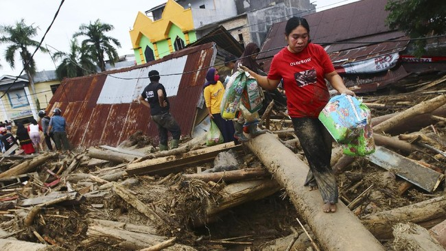 People walk on debris at an area affected by flash flood in Masamba, South Sulawesi province, Indonesia, Wednesday, July 15, 2020. Rescuers on Wednesday were searching for missing people after heavy rains in Indonesia's South Sulawesi province swelled rivers and send floodwaters, mud and debris across roads and into thousands of homes. (AP Photo/Khaizuran Muchtamir)