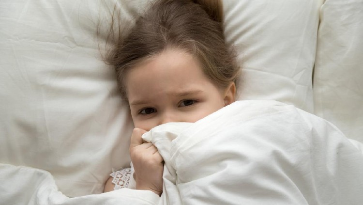 Cute little girl waking up in morning after sleep, covering face with blanket, preschool child lying in comfortable bed with white linens, looking at camera, top view from above close up