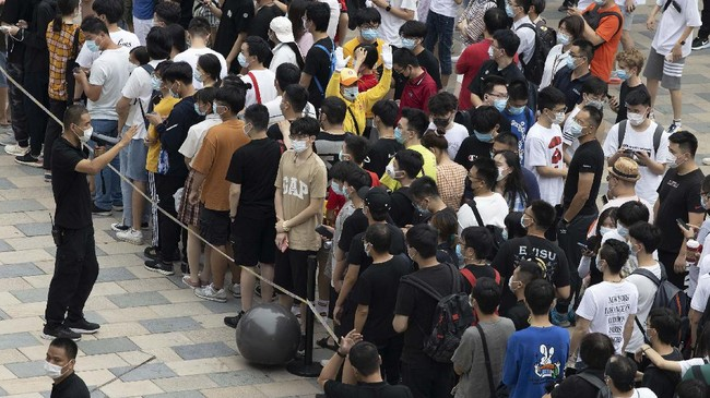 Workers try to control the crowd of Apple fans lining up to visit a new flagship store opened at Sanlitun in Beijing, China on Friday, July 17, 2020. China's economy rebounded from a painful contraction to grow by 3.2% over a year earlier in the latest quarter as anti-virus lockdowns were lifted and factories and stores reopened. (AP Photo/Ng Han Guan)