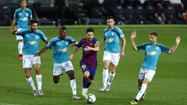 Barcelona's Lionel Messi, center, controls the ball by Osasuna's Pervis Estupinan, center left, during a Spanish La Liga soccer match between Barcelona and Osasuna at the Camp Nou stadium in Barcelona, Spain, Thursday, July 16, 2020. (AP Photo/Joan Monfort)
