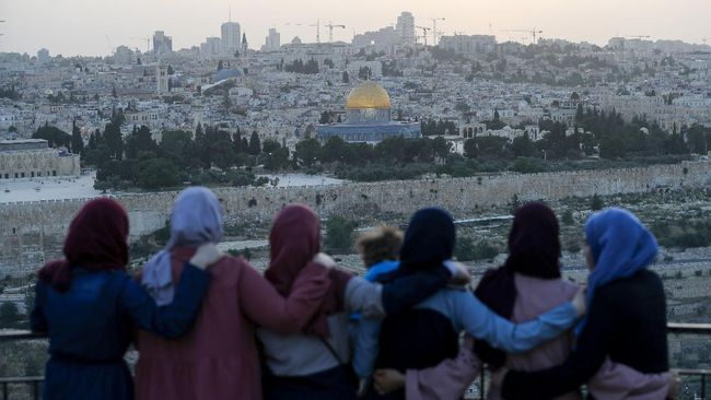 Palestinians gather to break their fast during the Muslim holy month of Ramadan, at the Mount of Olives with a backdrop of the Old City of Jerusalem and the closed al-Aqsa Mosque compound on May 19, 2020, during the novel coronavirus pandemic crisis. (Photo by Ahmad GHARABLI / AFP)