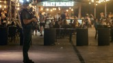 A Guardia Civil officer holds his weapons as tourists stand in a bar at the resort of Magaluf on the Spanish Balearic island of Mallorca, Spain, Thursday morning, July 16, 2020. Authorities in Spain's Balearic Islands are pulling the plug on endless drunken nights to the beat of techno music by closing bars and nightclubs in beachfront areas popular with young and foreign visitors. (AP Photo/Joan Mateu)