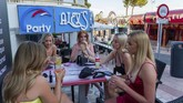 Tourists sit in a bar at the resort of Magaluf, in Punta Ballena town, on the Spanish Balearic island of Mallorca, Spain, Wednesday, July 15, 2020. Authorities in Spain's Balearic Islands are pulling the plug on endless drunken nights to the beat of techno music by closing bars and nightclubs in beachfront areas popular with young and foreign visitors. (AP Photo/Francisco Ubilla)