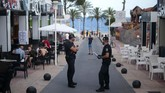 Police officers patrol at the resort of Magaluf on the Spanish Balearic island of Mallorca, Spain, Thursday, July 16, 2020. In a move designed to stop the spread of the new coronavirus and shake off the region's reputation as a party hub, regional authorities in the Balearic Islands ordered the closure from Thursday of all establishments along Mallorca's