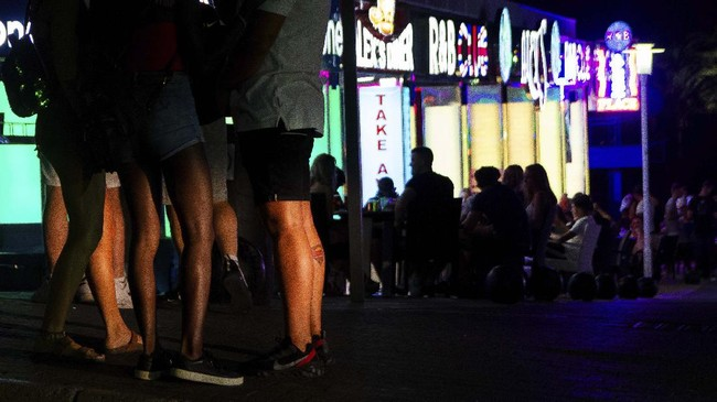 Tourists stand in a terrace at the resort of Magaluf on the Spanish Balearic island of Mallorca, Spain, Thursday, July 16, 2020. Authorities in Spain's Balearic Islands are pulling the plug on endless drunken nights to the beat of techno music by closing bars and nightclubs in beachfront areas popular with young and foreign visitors. (AP Photo/Francisco Ubilla)