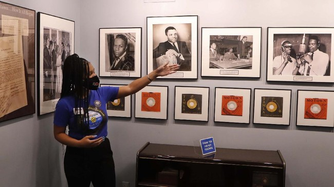 Motown Museum tour guide Jamia Henry points out notable Motown legends during a tour of the museum, Wednesday, July 15, 2020, in Detroit. The Detroit building where Berry Gordy Jr. built his music empire reopened its doors to the public on Wednesday. It had been closed since March due to the coronavirus pandemic. (AP Photo/Carlos Osorio)