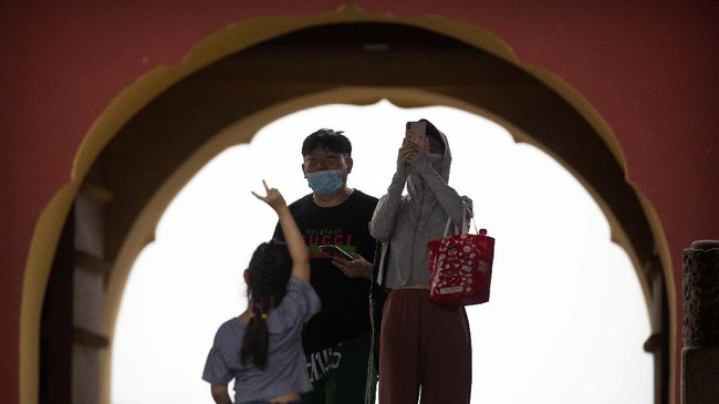 People wearing face masks to protect against the coronavirus take photos at the Temple of Heaven in Beijing, Saturday, July 18, 2020. Authorities in a city in far western China have reduced subways, buses and taxis and closed off some residential communities amid a new coronavirus outbreak, according to Chinese media reports. They also placed restrictions on people leaving the city, including a suspension of subway service to the airport. (AP Photo/Mark Schiefelbein)
