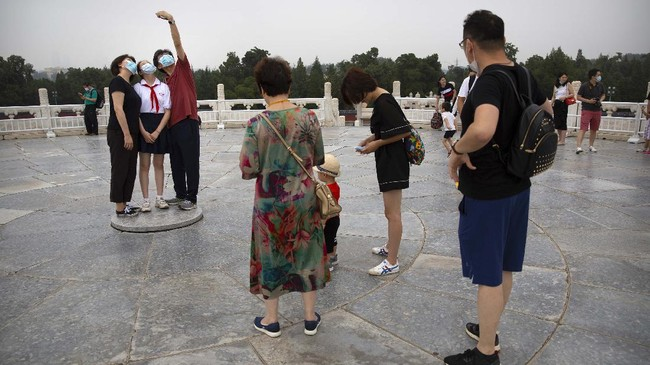 People wearing face masks to protect against the coronavirus pose for a selfie at the Temple of Heaven in Beijing, Saturday, July 18, 2020. Authorities in a city in far western China have reduced subways, buses and taxis and closed off some residential communities amid a new coronavirus outbreak, according to Chinese media reports. They also placed restrictions on people leaving the city, including a suspension of subway service to the airport. (AP Photo/Mark Schiefelbein)