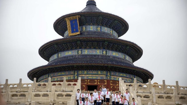 Students pose for a group photo at the Temple of Heaven in Beijing, Saturday, July 18, 2020. Authorities in a city in far western China have reduced subways, buses and taxis and closed off some residential communities amid a new coronavirus outbreak, according to Chinese media reports. They also placed restrictions on people leaving the city, including a suspension of subway service to the airport. (AP Photo/Mark Schiefelbein)