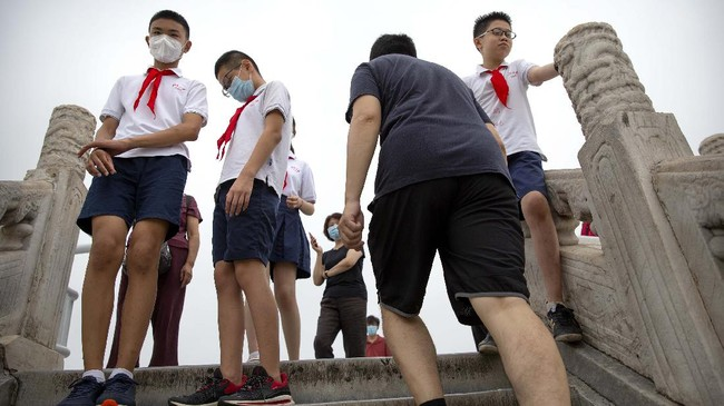 Students wearing face masks to protect against the coronavirus gather at the Temple of Heaven in Beijing, Saturday, July 18, 2020. Authorities in a city in far western China have reduced subways, buses and taxis and closed off some residential communities amid a new coronavirus outbreak, according to Chinese media reports. They also placed restrictions on people leaving the city, including a suspension of subway service to the airport. (AP Photo/Mark Schiefelbein)
