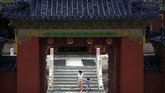 A woman and child wearing face masks to protect against the coronavirus walk through the Temple of Heaven in Beijing, Saturday, July 18, 2020. Authorities in a city in far western China have reduced subways, buses and taxis and closed off some residential communities amid a new coronavirus outbreak, according to Chinese media reports. They also placed restrictions on people leaving the city, including a suspension of subway service to the airport. (AP Photo/Mark Schiefelbein)