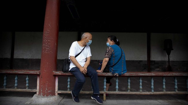 People wearing face masks to protect against the coronavirus sit on a railing at the Temple of Heaven in Beijing, Saturday, July 18, 2020. Authorities in a city in far western China have reduced subways, buses and taxis and closed off some residential communities amid a new coronavirus outbreak, according to Chinese media reports. They also placed restrictions on people leaving the city, including a suspension of subway service to the airport. (AP Photo/Mark Schiefelbein)