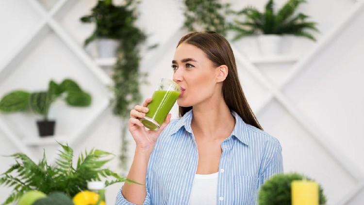 Healthy lifestyle. Woman drinking smoothie, sitting in kitchen, having lunch