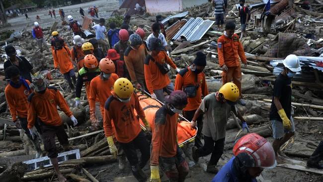 Tim SAR gabungan mengangkat kantong jenazah korban banjir bandang di Desa Radda, Kabupaten Luwu Utara, Sulawesi Selatan, Sabtu (18/7/2020). Proses pencarian korban banjir bandang terkendala material lumpur dan curah hujan yang masih sering terjadi, sementara tim SAR telah menemukan 36 korban meninggal dunia dan 18 orang lainnya masih terus dilakukan pencarian. ANTARA FOTO/Abriawan Abhe/wsj.