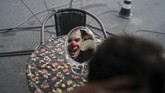 Anderson de Souza, the clown Batatinha, grimaces to the mirror as he puts on his clown face before performing at the Estoril Circus amid the new coronavirus pandemic in Itaguai, greater Rio de Janeiro, Brazil, Saturday, July 18, 2020.