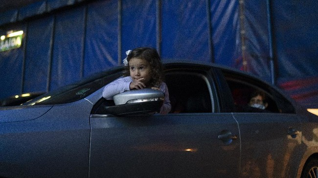 A child watches from inside the car artists performing at the Estoril Circus in a drive-in format amid the new coronavirus pandemic in Itaguai greater Rio de Janeiro, Brazil, Saturday, July 18, 2020. Following the measures to curb the spread of the COVID-19, artists of this circus have decided to go back to work in a different way, as a circus drive-in. (AP Photo/Leo Correa)