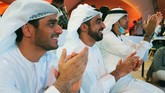 Emirati men claps as they watch the launch of the