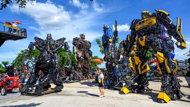 This photograph taken on July 18, 2020 shows tourists taking photos of life-sized sculptures of characters from the