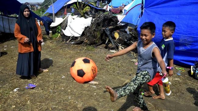 Petugas-relawan berjibaku meringankan trauma anak-anak di pengungsian korban banjir bandang Luwu Utara. BNPB menduga banjir itu akibat alih fungsi lahan.