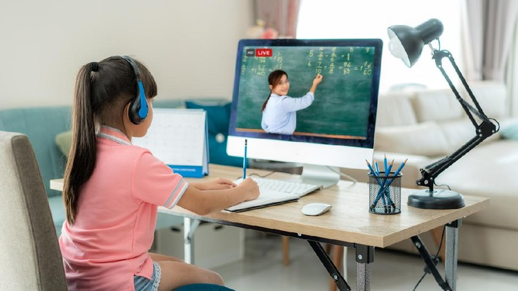 Asian  student girl video conference e-learning with teacher on computer in living room at home. E-learning ,online ,education and internet social distancing protect from COVID-19 virus.
