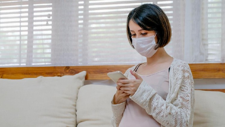 Asian pregnant woman with mask look at mobile phone and sit on sofa in living room of her house with soft light.