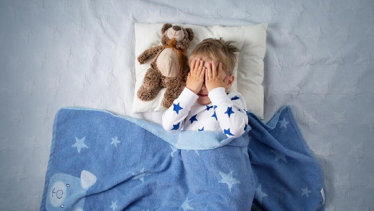 Three years old child crying in bed. Sad boy on pillow in bedroom