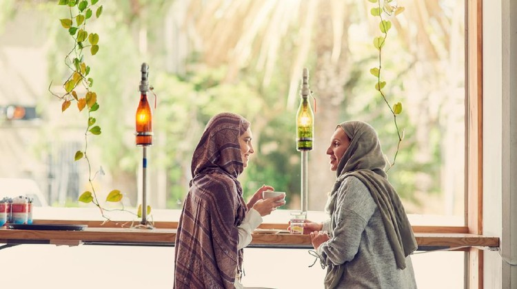 Shot of two women chatting over coffee in a cafe