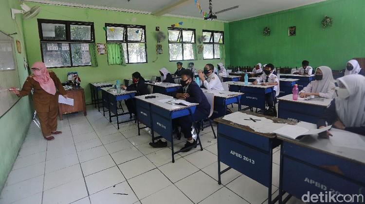 Siswa Siswi mengikuti simulasi sekolah percontohan pembelajaran tatap muka di SMP Negeri 2 Bekasi, Jawa Barat, Senin (3/8/2020). Pelaksanaan ini dilaksanakan mulai hari ini hingga 28 Agustus 2020. Siswa yang yang mengikuti pelajaran tatap muka hari ini 18 anak perkelas.  setiap kelas 7, 8 dan 9 diwakili 1 kelas yang bergantian setiap harinya.