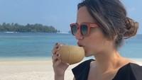 <p>Minum air kelapa muda di pinggir pantai, pasti segar banget ya, Bunda. (foto: Instagram @ramadhaniabakrie)</p>