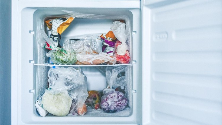 Shot of an open freezer packed with frozen food in plastic bags