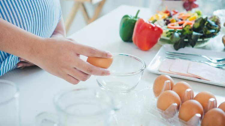 Woman cracking an egg into a bowl with  standing by in kitchen. Mother pregnant cooking in kitchen.