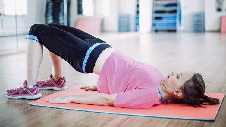 Portrait of serious young Caucasian woman wearing sportswear doing abdominal exercise lying on mat in gym