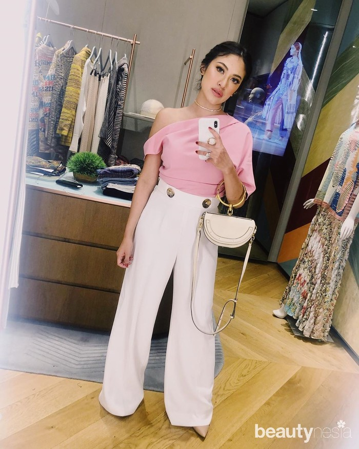 Cynthia kali ini mengenakan atasan sabrina merah muda dengan palazzo putih lengkap dengan handbag di lengannya. Tampilannya selalu terlihat simpel namun elegan. Gaya makeupnya juga menyesuaikan dengan warna outfit yang dipakainya. (Foto: Instagram.com/Cynthiaganesha)