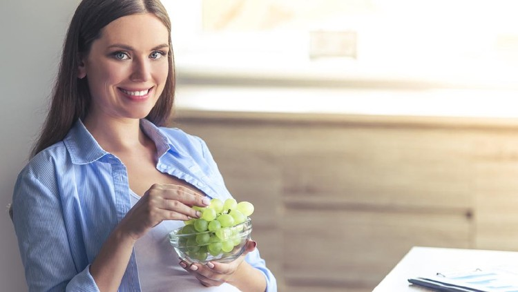 Beautiful pregnant business woman is eating grape, looking at camera and smiling while sitting at her working place at home