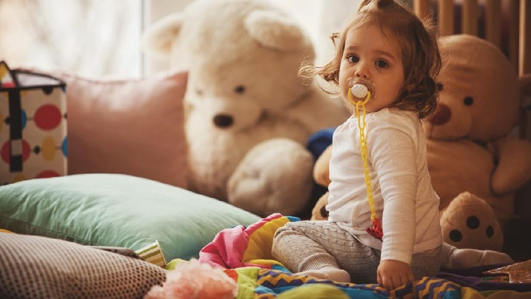 Copy space shot of little girl with pacifier sitting on the floor of living room. She is surrounded with stuffed toys and soft pillows.