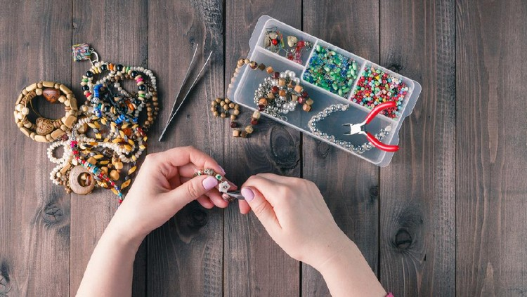 Making of handmade jewellery. Box with beads on old wooden background. Handmade accessories. Top view