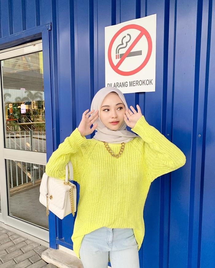 Kalau potret berikut ini memang terkesan masing ABG ya. Mengenakan atasan bahan rajut warna kuning , bawahan jeans dan hijab polos membuat Adira terlihat simpel dan kekinian. Tidak lupa, ia bergaya seperti sedang membenarkan hijab sehingga telihat lebih cute. (Foto: instagram.com/adirasalahudi)