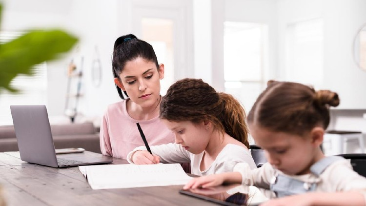 A confident mid adult mom teaches her two young daughters at home while under stay-at-home order during coronavirus crisis.