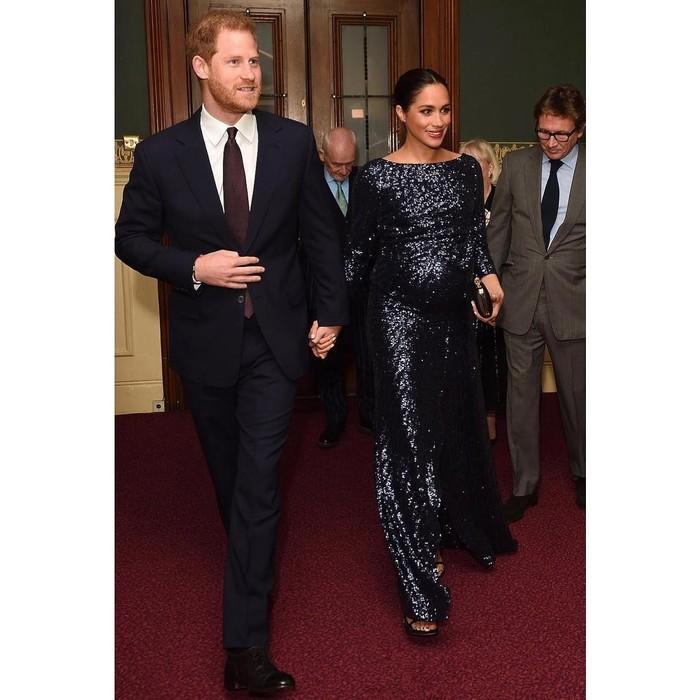 Tampil dengan sequin dress berwarna navy, penampilan Meghan Markle saat menghadiri acara di Royal Albert Hall ini tampak begitu memukau dan elegan. Ia diketahui mengenakan gaun malam dari Roland Mouret seharga US$5.595 atau Rp79 juta dan heels seharga US$398 atau Rp5,5 juta dari Stuart Weitzman. (Foto: instagram.com/kensingtonroyal)