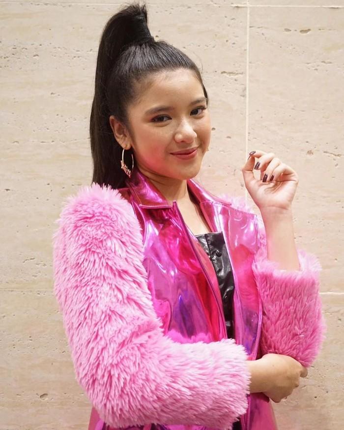 Tren 90-an juga identik dengan bahan fur. Seperti Tiara Andini yang terlihat cantik saat memakai jaket rasfur berwarna pink dengan sentuhan model blazer plastik PVC pink yang berkilau. Pada bagian tengah diberi detail potongan berwarna hitam supaya outfit enggak terlihat monoton. (Foto: www.instagram.com/tiaraandini/)