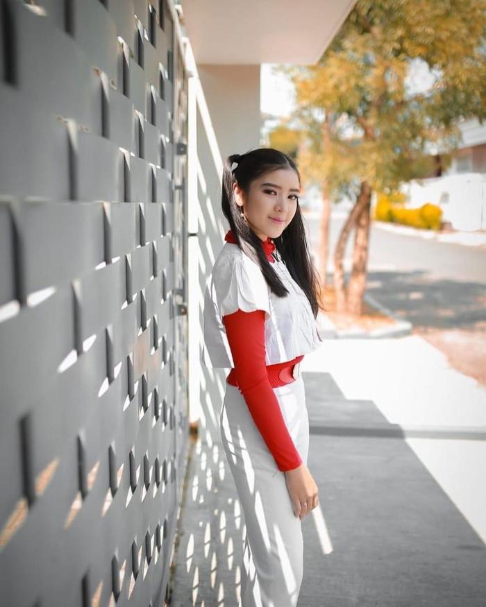 Inspirasi fashion juara 2 Indonesian Idol kali ini memadukan crop tee lengan pendek putih dan inner berwarna merah. Kombinasikan dengan skinny pants dan voila tampilan fashion 90-an pun bisa didapatkan. (Foto: www.instagram.com/tiaraandini/)