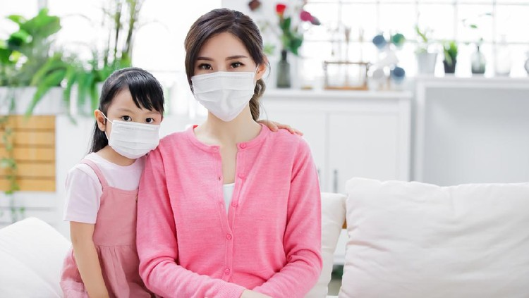 Mom and daughter wear mask to protect themselves from virus infection