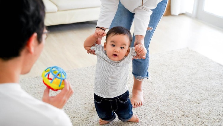 Asian baby boy toddler taking first steps. Family of father and mother encouraging their son learning to walk at home
