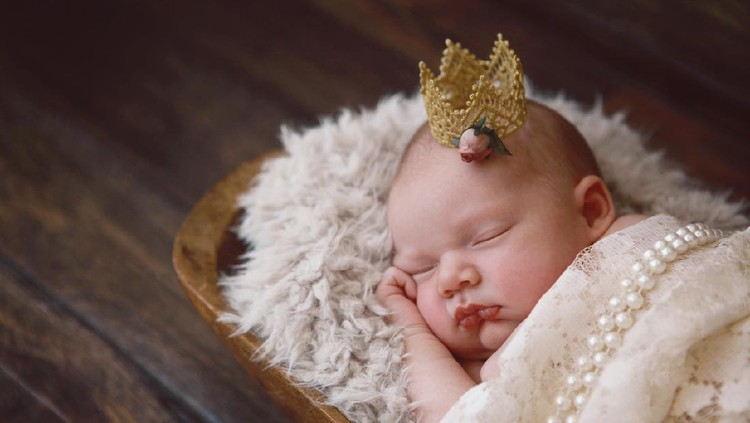 A newborn baby girl sleeps soundly. She is wearing a tiny golden crown. A princess is born!