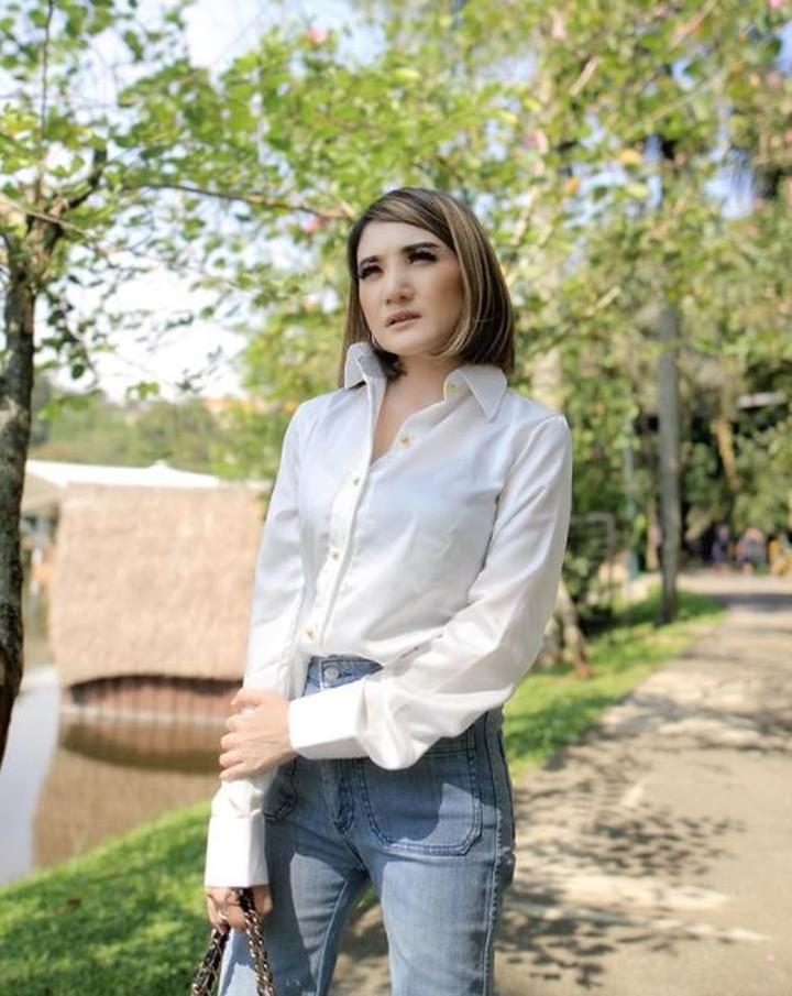 Meski hanya mengenakan kemeja putih dan celana jeans, penampilan Kiki tetap modis ya. (Foto: Instagram @kikiamaliaworld)