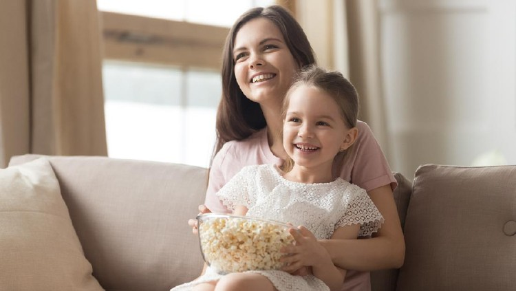 Happy young mom and child girl laughing holding snack popcorn remote control enjoy funny television comedy movie, smiling family mother with kid girl watching fun humor tv show laugh sitting on sofa