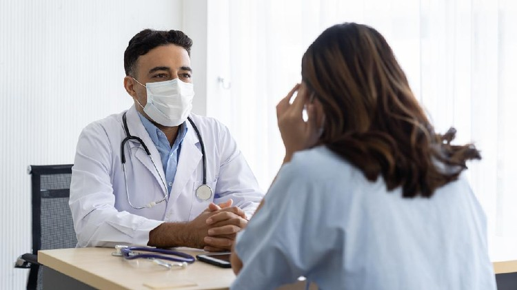 Male doctor wearing face mask discussing with woman patient while sitting on the table in the office at the hospital